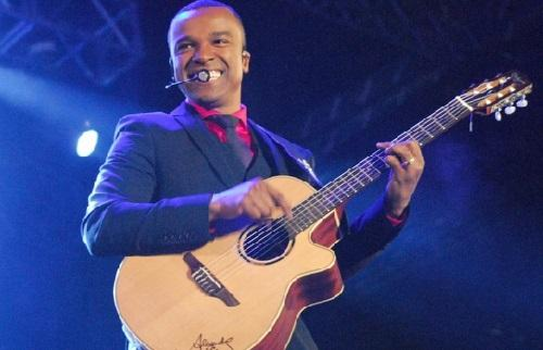 foto del cantante brasileno Alexandre Pires cantando con guitarra